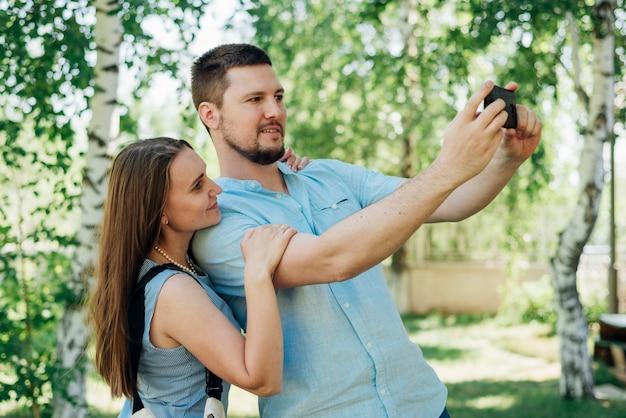 Happy couple shooting selfie in park Free Photo