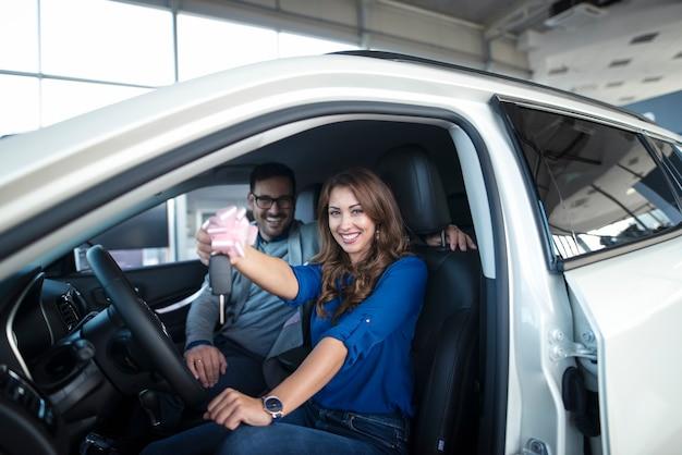 Coppia felice seduto in una macchina nuova che hanno appena comprato e tenendo le chiavi Foto Gratuite
