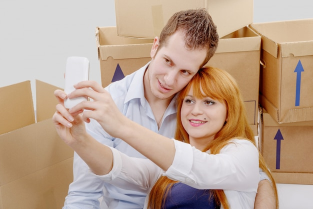 Happy couple sitting on the floor taking selfie in their new house Premium Photo