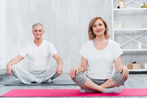 Happy couple sitting at home on yoga mat Free Photo