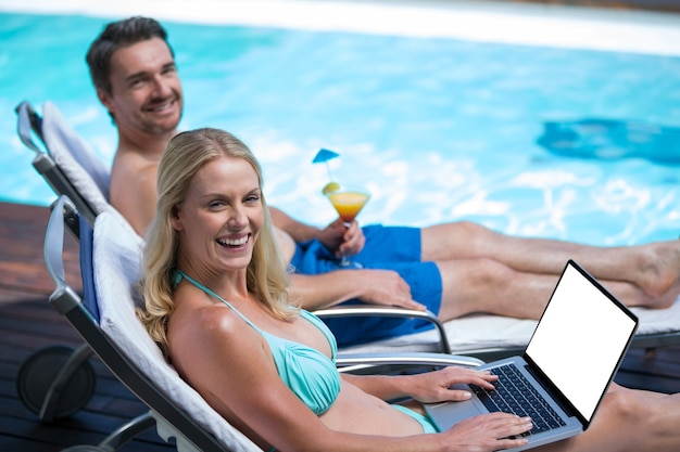 プールの近くのサンラウンジャーに座っている幸せなカップル Premium写真