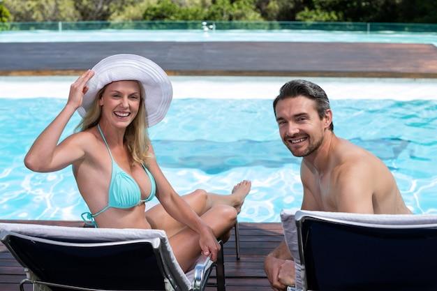 サンラウンジャーに座っている幸せなカップル Premium写真