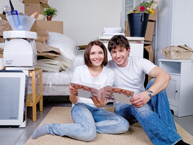 Счастливая пара, сидя на полу вместе с фотоальбомом Бесплатные Фотографии