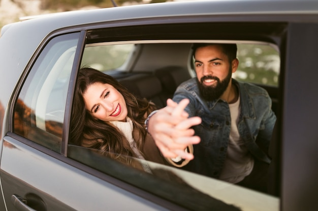 Happy couple sitting on rear seats Free Photo