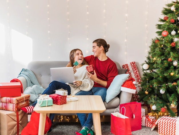 Happy couple sitting with laptop and credit card on couch Free Photo