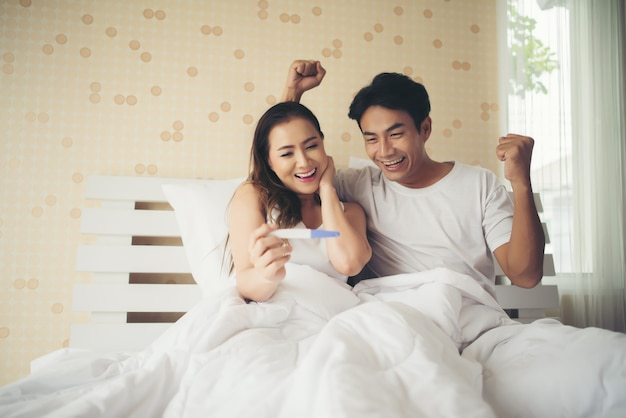 Happy couple smiling after find out positive pregnancy test in bedroom Free Photo