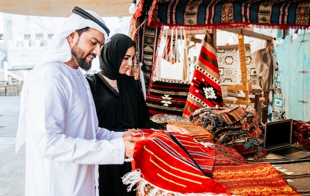 Happy couple spending time in dubai. man and woman wearing traditional clothes making shopping in the old city Premium Photo