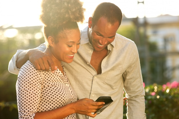 Happy couple standing outside looking at message on phone Premium Photo