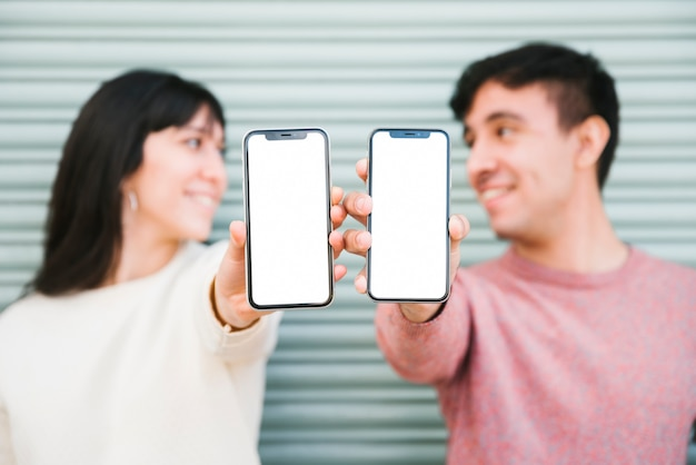 Happy couple standing with smartphones Free Photo