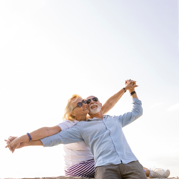 Happy couple stretching their arms in the air Premium Photo