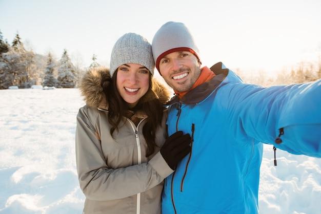Счастливая пара, делающая селфи на снежном пейзаже Бесплатные Фотографии