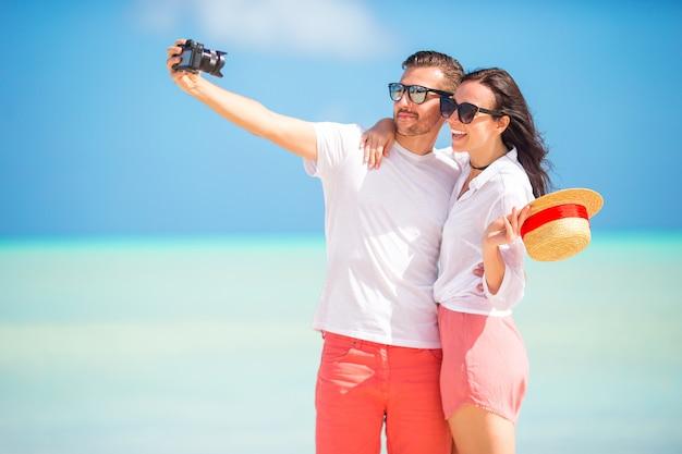 Happy couple taking a photo on white beach on honeymoon holiday Premium Photo
