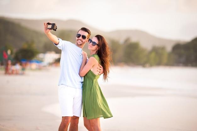 Happy couple taking a photo on white beach on honeymoon holidays Premium Photo