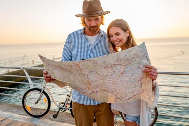 Счастливая пара путешествует летом на велосипедах, глядя на карту достопримечательностей Бесплатные Фотографии
