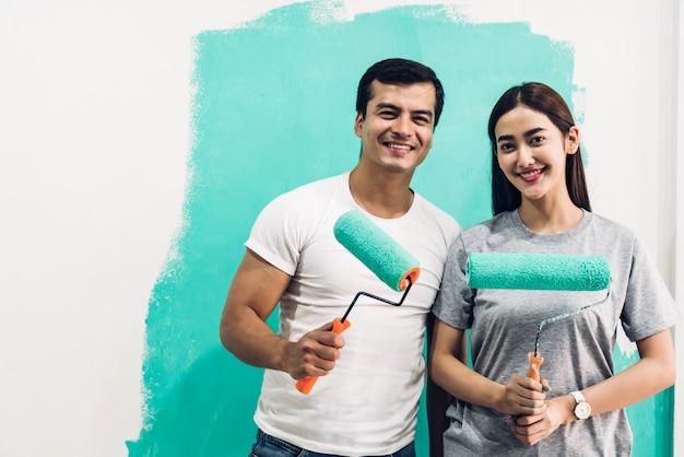 彼らの新しい家でペイントローラーと絵画の壁を使用して幸せなカップル Premium写真
