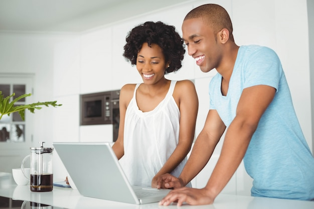 Happy couple using laptop in the kitchen on the counter Premium Photo