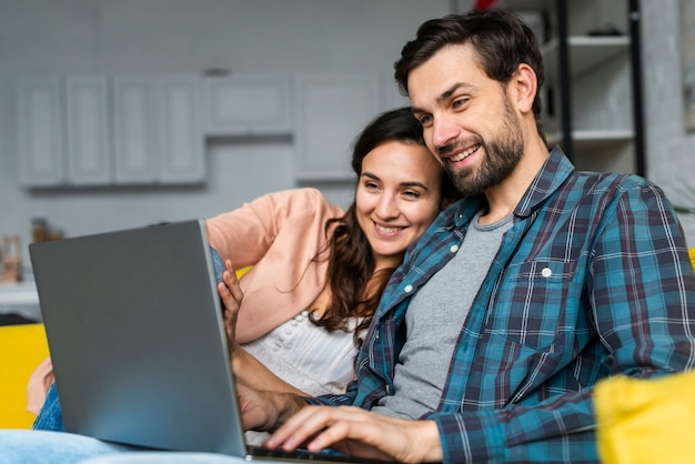 Happy couple using the laptop Free Photo