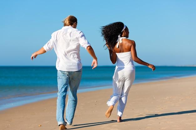 Happy couple walking and running on beach Premium Photo