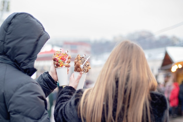 Happy couple in warm clothes in love eating bubble waffles at christmas fair. holidays, winter, christmas and people Premium Photo