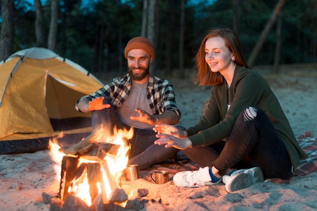 Happy couple warming up by campfire Free Photo