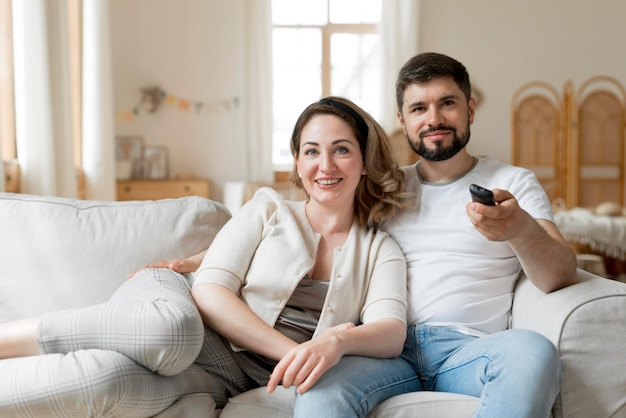 Happy couple watching tv together Free Photo