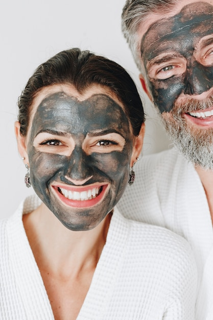 Happy couple wearing a charcoal mask Premium Photo