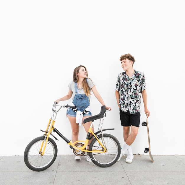 Happy couple with bicycle and skateboard looking at each other Free Photo