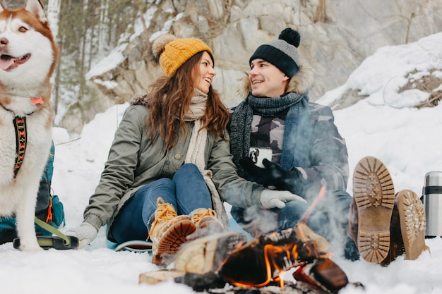 The happy couple with dog haski at the forest nature park in cold season. travel adventure love story Premium Photo