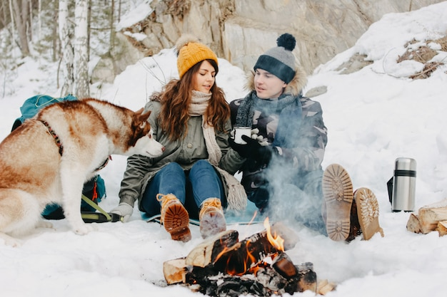 Happy couple with dog haski at the forest nature park in cold season. Premium Photo