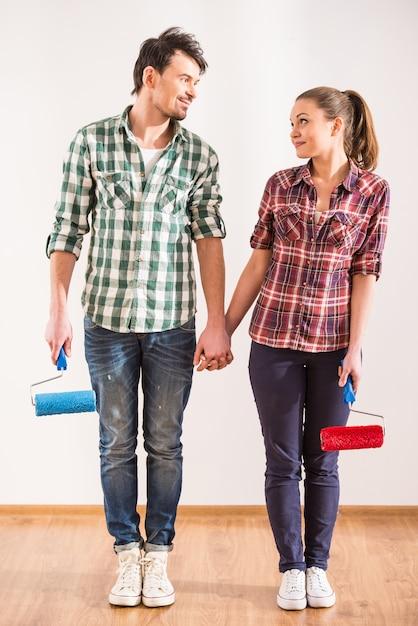 Счастливая пара с валиком смотрят друг на друга. Premium Фотографии