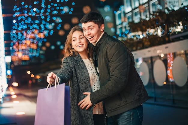 Le coppie felici con i sacchetti della spesa che godono della notte alla città Foto Gratuite