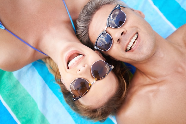 Happy couple with sunglasses on the beach Free Photo
