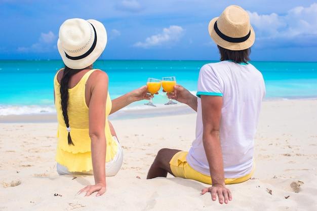 Happy couple with two glasses of orange juice on beach vacation Premium Photo