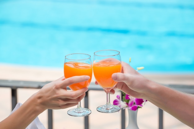 Happy couple with two glasses of orange juice at swiming pool vacation Premium Photo