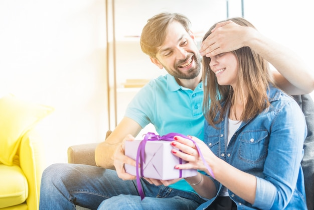 Happy couple with valentine gift sitting on sofa Free Photo
