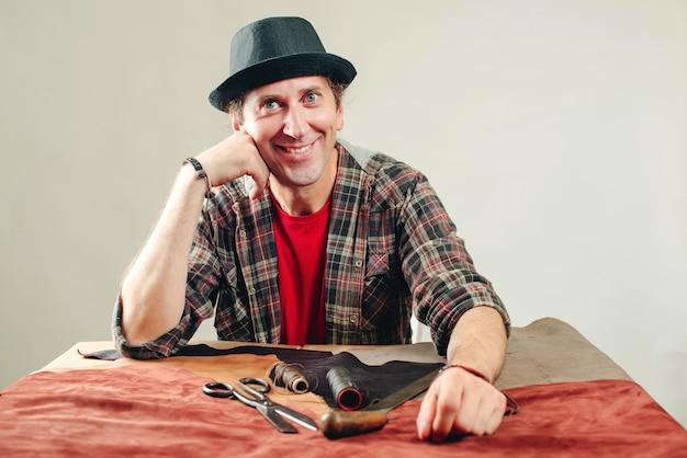 Счастливый мастер на рабочем месте. работник создает новое изделие из кожи в мастерской. инструменты для крафта, кожа на столе. ручной инструмент. малый бизнес Premium Фотографии