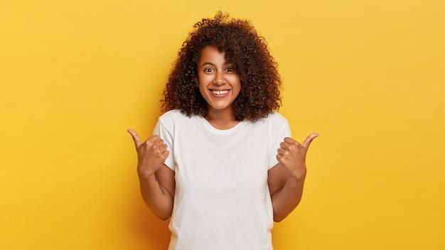 Счастливая кудрявая девушка показывает палец вверх, демонстрирует кому-то поддержку и уважение, приятно улыбается, добивается желаемой цели, носит белую футболку, изолированную на желтой стене Бесплатные Фотографии
