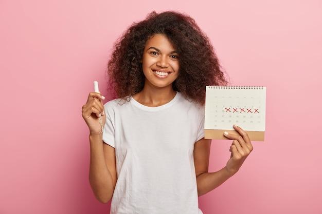 행복한 곱슬 머리 아가씨는 분홍색 배경 위에 절연 캐주얼 흰색 티셔츠를 입은 표시된 Pms 일과 탐폰으로 생리 달력을 보유하고 있습니다. 무료 사진
