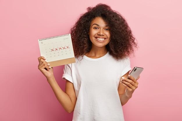 幸せな巻き毛の女性は生理カレンダーを保持します 無料写真