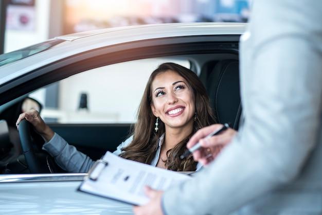 Happy customer buying brand new car at local car dealership Free Photo