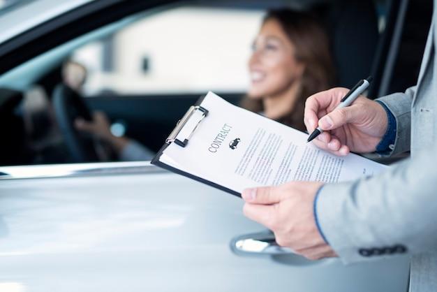 Cliente felice che acquista un'auto nuova di zecca presso un concessionario di automobili locale Foto Gratuite
