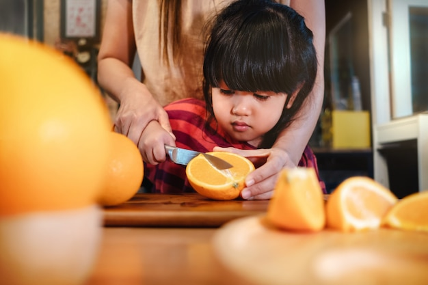 Happy cute 3-4 years old girl with her mom slice some orange on wooden table in pantry room. young girl is learning cook with her mother. fruit and vegetable for kids concept Premium Photo
