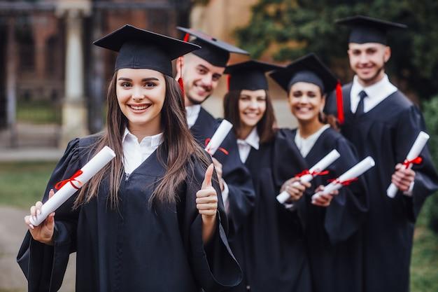 Happy cute brunette caucasian grad girl is smiling, blurred class mates are behind Premium Photo