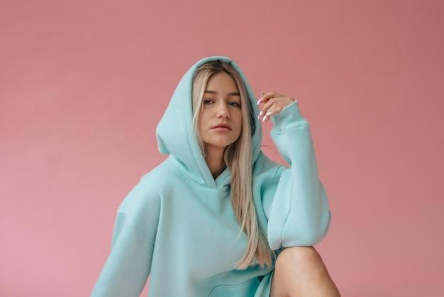 Счастливая милая девушка, одетая в синий наряд, сидя на розовом фоне в студии. Premium Фотографии
