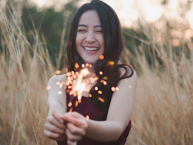 Happy cute girl holding a sparkler in the dry grass field