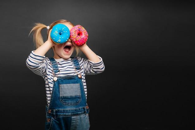 행복 한 귀여운 소녀 재미 검은 배경 벽에 도넛으로 연주입니다. 아이의 밝은 사진. 컬러 도넛 프리미엄 사진