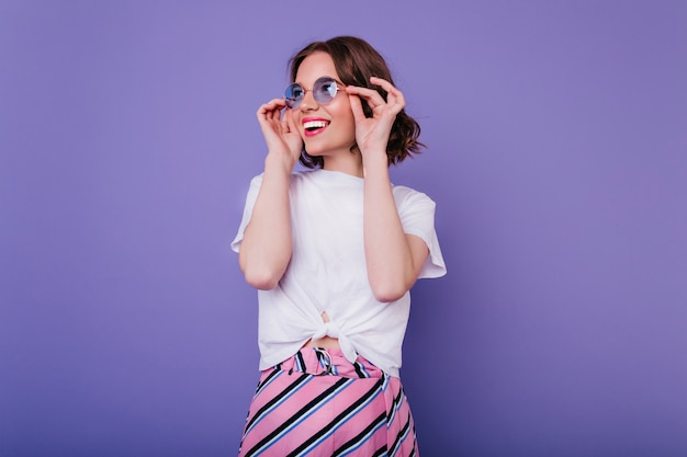 Happy cute girl with wavy hairstyle touching her glasses with smile. indoor shot of magnificent curly lady in white t-shirt posing on purple wall. Free Photo