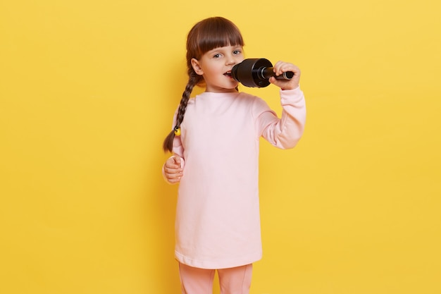 Happy cute little girl singing song on microphone while posing isolated over yellow background, dark haired female chile with pigtails sings in karaoke, looking at camera with excited and happy look. Free Photo