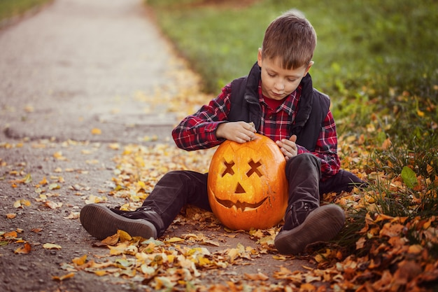 Happy cute little kid boy with halloween pumpkin in autumn park. Premium Photo
