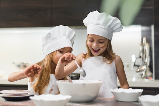 Happy cute siblings preparing food on kitchen worktop Free Photo